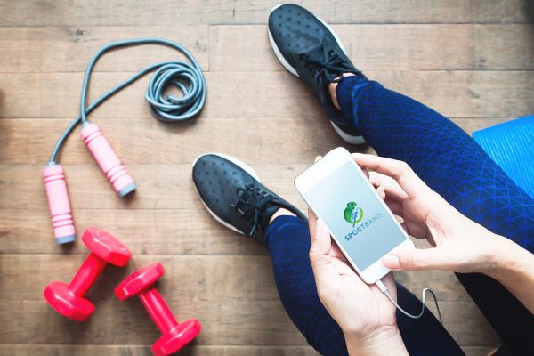 Woman in fitness clothing using smartphone. Fitness and Diet, Gym and Workout concept